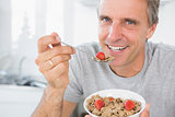 Cheerful man eating cereal for breakfast