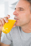 Content man drinking orange juice in kitchen