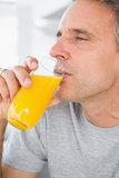 Content man drinking orange juice in kitchen