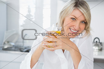 Smiling blonde having orange juice in kitchen