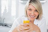 Happy blonde having orange juice in kitchen