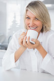 Cheerful woman having coffee in the morning
