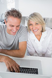 Smiling couple using their laptop in the morning