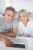 Smiling couple using their laptop in the morning looking at camera