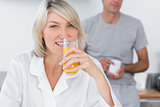 Blonde drinking orange juice in kitchen