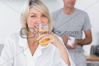 Blonde drinking orange juice in kitchen
