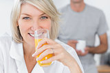 Happy woman drinking orange juice in kitchen