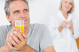 Smiling man drinking orange juice in kitchen
