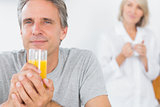 Happy man drinking orange juice in kitchen