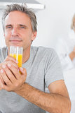 Cheerful man drinking orange juice in kitchen