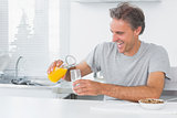 Happy man pouring orange juice for breakfast