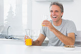 Happy man having orange juice with breakfast