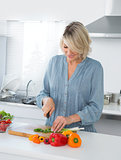Cheerful woman preparing vegetables