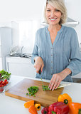 Cheerful woman chopping vegetables