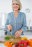 Smiling woman chopping vegetables
