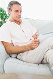 Cheerful man on his couch using tablet pc