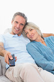Cheerful couple on their couch watching tv