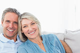 Cheerful couple relaxing on their couch