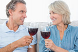 Couple toasting each other with red wine on the sofa