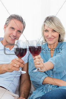 Couple toasting to the camera with red wine on the couch