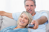 Cheerful couple relaxing at home watching tv
