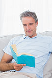 Man relaxing on his sofa with a book