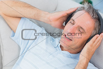 Man lying on sofa listening to music with eyes closed