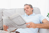 Man reading the newspaper on couch