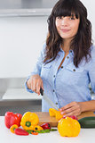 Pretty brunette slicing vegetables