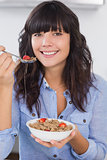 Pretty brunette having bowl of cereal and fruit