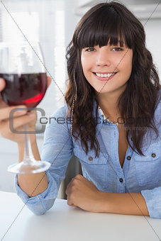 Attractive brunette having glass of red wine