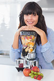 Smiling brunette leaning on her juicer full of fruit