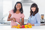 Cheerful friends preparing vegetables