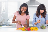 Cheerful friends preparing a salad together