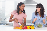 Laughing friends preparing a salad together