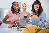 Laughing friends making spaghetti dinner together and drinking red wine