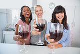 Cheerful friends toasting to the camera with glasses of red wine