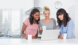 Smiling friends having coffee together and looking at laptop