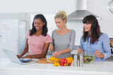 Smiling friends making salad and using laptop for recipe