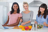 Cheerful friends making salad and using laptop for recipe looking at camera
