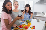 Cheerful friends preparing a meal together and drinking red wine