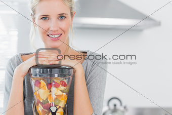 Blonde woman leaning on her juicer and smiling at camera