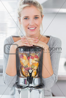 Blonde woman leaning on her juicer full of fruit and smiling at camera