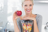 Blonde woman leaning on her juicer full of fruit and holding red apple