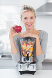 Pretty woman leaning on her juicer full of fruit and holding red apple