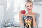 Happy woman leaning on her juicer full of fruit and holding red apple