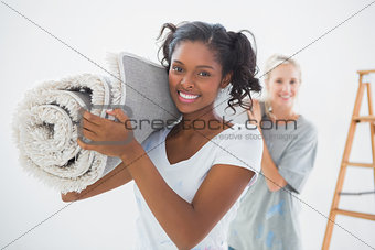 Housemates carrying rolled up rug