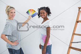 Housemates picking colour for blank wall and smiling at camera
