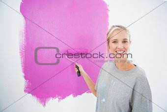 Smiling blonde painting her wall pink