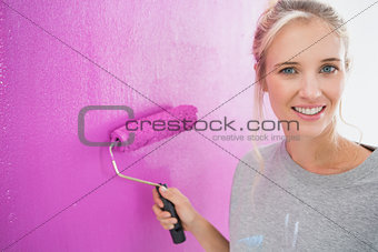 Cheerful blonde painting her wall pink